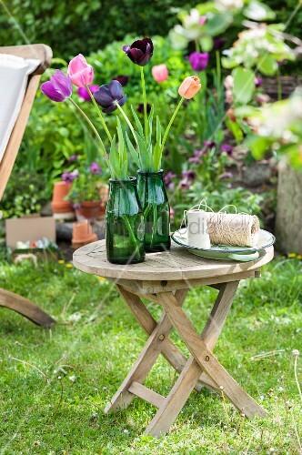 Tulips in green glass vases on garden table