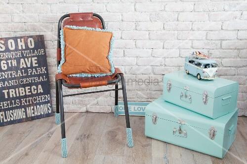 Mintfarbene Koffer, Lederstuhl mit gestrickten Stulpen und Retro-Schilder