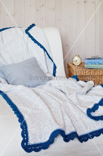 Grey and white patterned blanket with blue crocheted trim