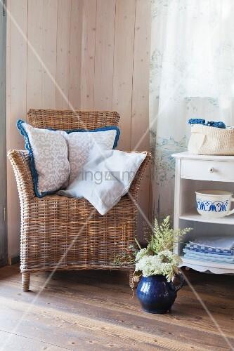 Korbstuhl mit umhäkelten Kissen im ländlichen Wohnzimmer