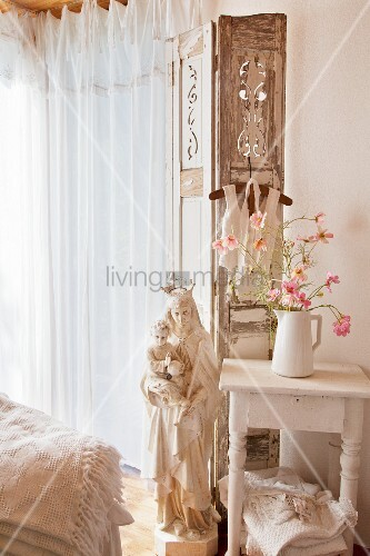 Flowers on side table and Madonna figurine in shabby-chic interior