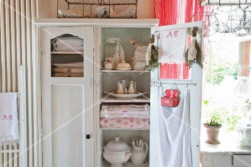 Table linen and kitchen utensils in old cupboard with open door