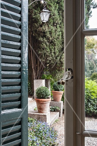 View through lattice window and shutters into garden