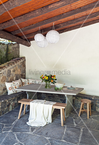 Table and bench on roofed terrace with stone-flagged floor