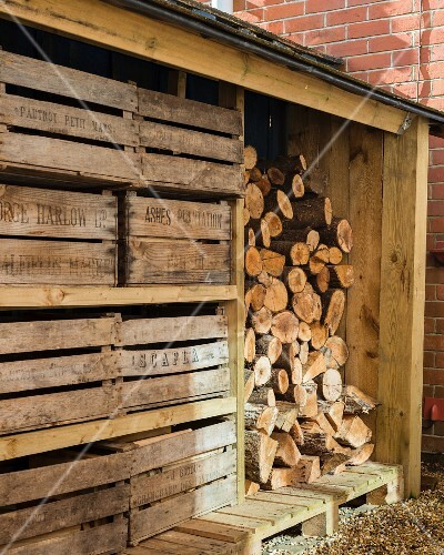 Weathered wooden crates next to stacked firewood in shed