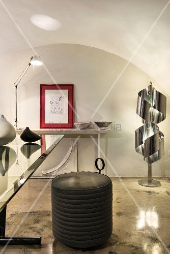 Black pouffe on glossy concrete floor in front of designer lamp and console table