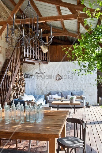 Country-house-style lounge area on roofed wooden terrace