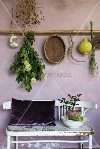 Mediterranean decorations hung from bamboo pole above old bench