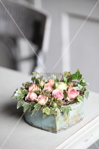Romantic arrangement of ivy and roses in vintage container