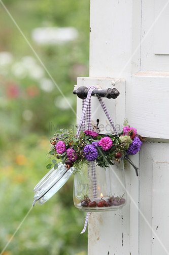 Candle lantern made from mason jar decorated with wreath of asters