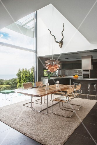 Modern dining table and cantilever chairs next to panoramic window