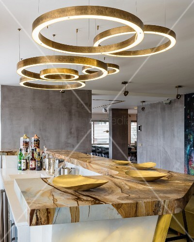 Circular brass light fittings above marble bar