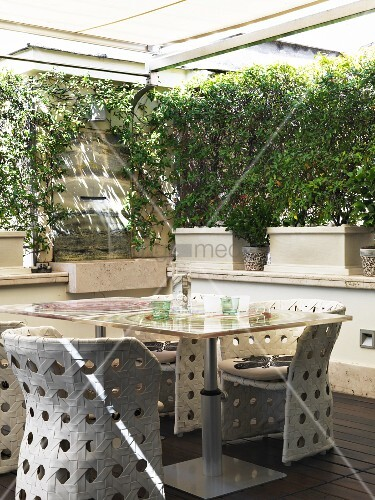 Garden table and woven outdoor chairs on sheltered terrace