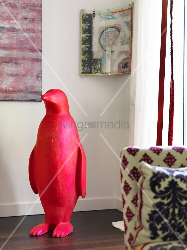 Red plastic penguin in front of modern artwork in corner of room