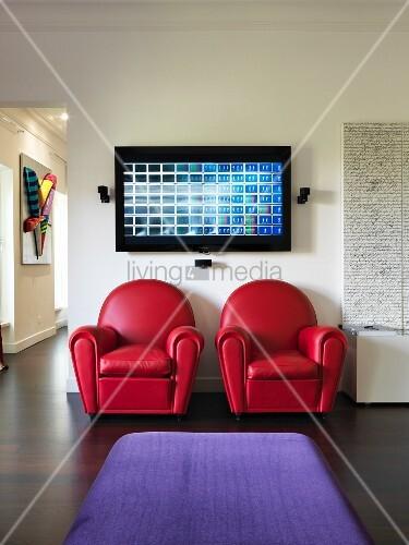 Red leather armchairs below digital artwork