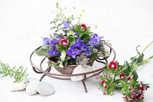 Arrangement of delphiniums and sweet Williams in metal dish