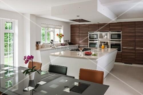 Moderne wohnk che mit kochinsel und dunklen holzfronten for Wohnkuche mit kochinsel