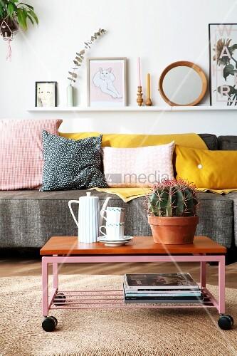 Fahrbarer Couchtisch mit Retro Geschirr und Kaktus auf Bastteppich vor Couch mit Dekokissen