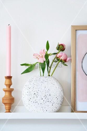 Gedrechselter Kerzenständer, rosa Kerze und gesprenkelter Vase mit Blumen auf Wandboard