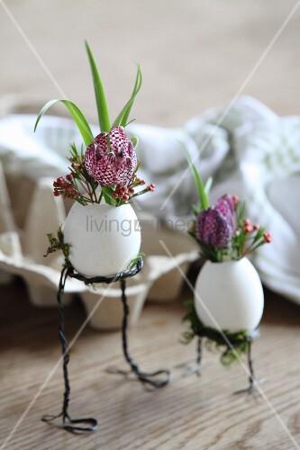 Flowers arranged in blown eggs on wire legs