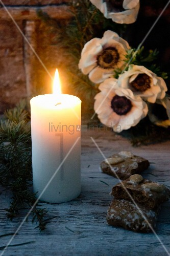 Lit Advent candle with number 1 on side, gingerbread and anemones