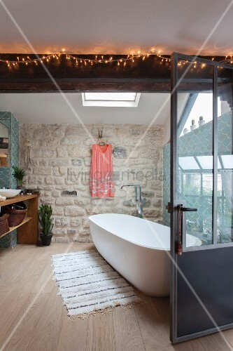 Exposed stone wall and oval free-standing bathtub in bathroom