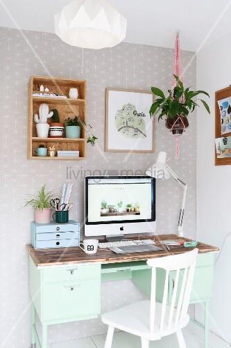 Mintfarbener Retro Schreibtisch mit Computerbildschirm und weisser Holzstuhl in Zimmerecke