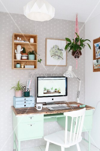 Monitor on mint-green retro desk and white wooden chair in corner