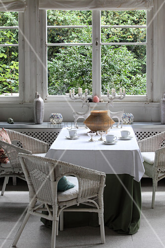 White wicker armchairs around table in conservatory