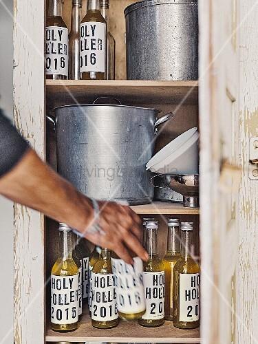 Homemade elder lemonade in labelled bottles in a vintage kitchen cupboard