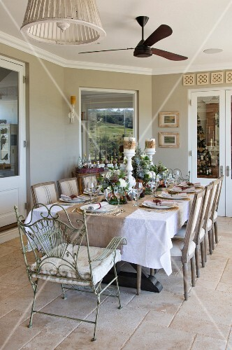 Table festively set for Christmas in room decorated in natural shades