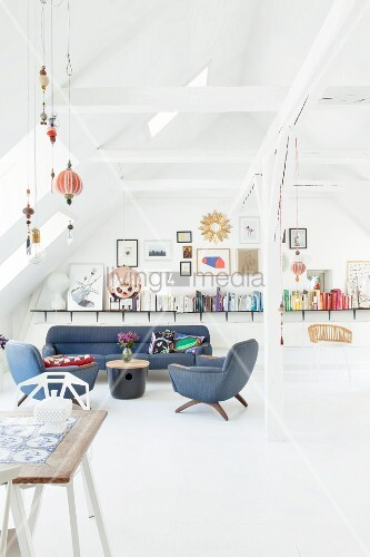 Retro furniture, dining area and long shelf on wall in renovated, white attic room