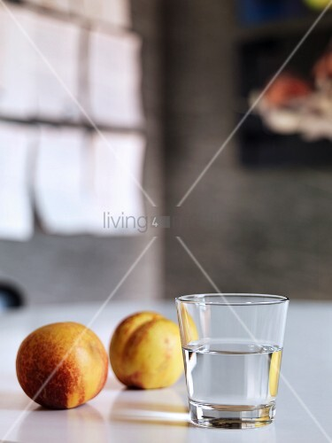 Glass of water and two nectarines