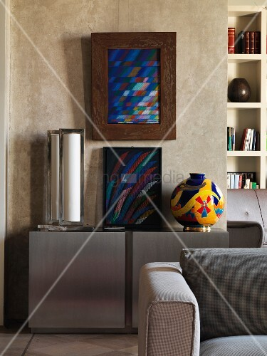 Modern artwork on modern sideboard against colour-washed wall