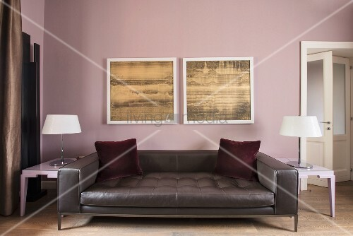 Red velvet scatter cushions on dark leather couch below two pictures on wall