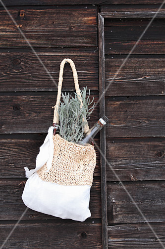 Hand-made cotton and raffia bag hung on wooden wall