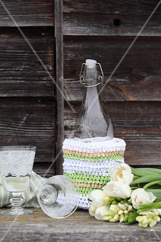 Bügelflasche mit gehäkelter Hülle aus Bast