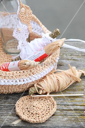 Gehäkelter Brotkorb aus Bast und Glasflasche mit gestrickten Fischen aus Bast