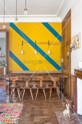 Yellow wall with diagonal stripes above dining table and wooden chairs