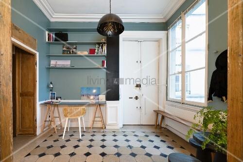 Schreibtisch auf Möbelböcken in einer Nische vor blauer Wand
