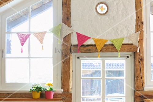 Crocheted bunting hung on half-timbered wall with lattice windows