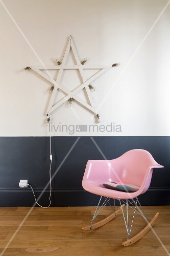 Pink rocking chair in front of star with lightbulbs on two-tone wall
