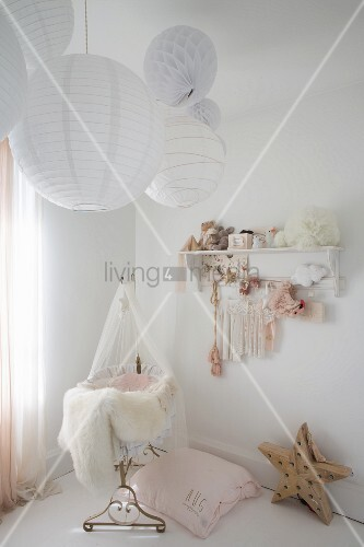 Paper lamps above cot in vintage-style nursery