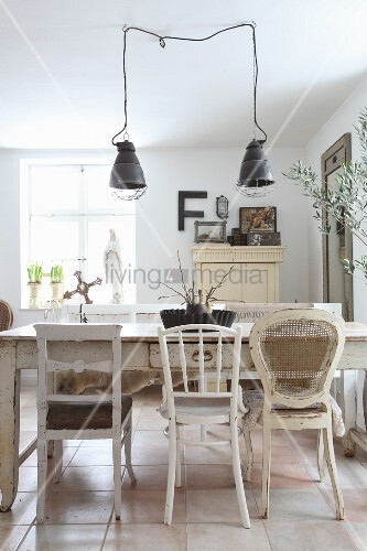 Various white chairs around old wooden table