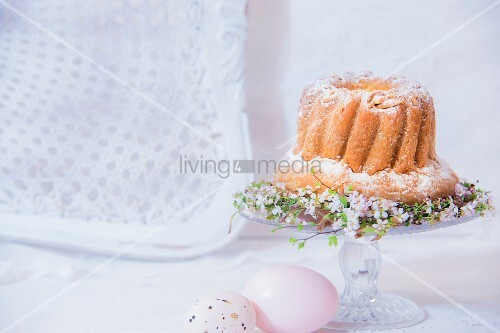 Bundt cake on decorated cake stand next to Easter eggs