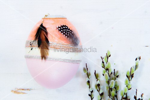 Painted egg decorated with ribbon and feathers next to willow catkins
