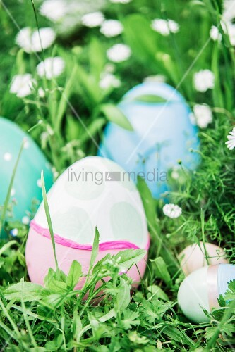 Easter eggs in pastel shades amongst grass