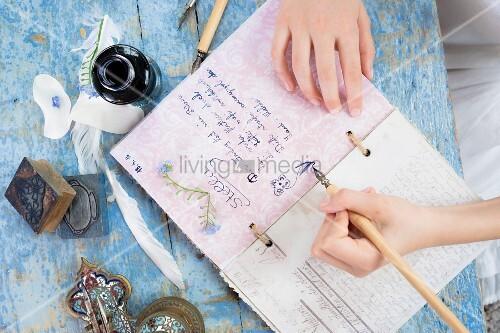 Hände schreiben mit einer Feder ins Poesiealbum, daneben das Tintenfaß
