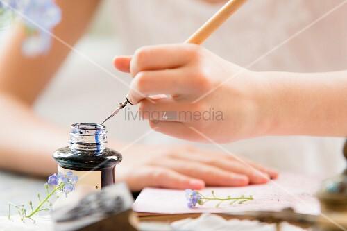 Hand taucht Feder in das Tintenfaß
