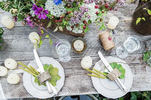 Gedeckter Tisch mit Wiesenblumen, Kerzen und Blättern